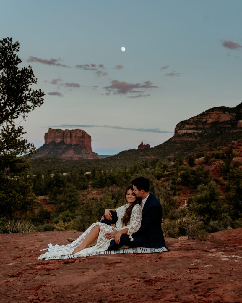Bride and groom relaxing as the moon rises over Sedona, Arizona on their elopement day