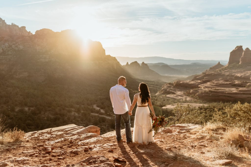 Bride and Groom holding hands overlooking the red rock canyons of Sedona, Arizona