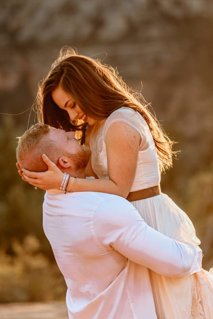 Bride gazing at her husband as he lifts her during sunset first dance