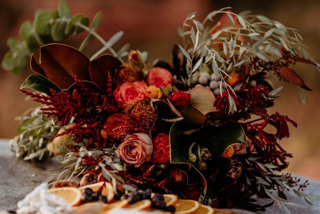 Red, orange, yellow, and deep burgundy wildflower wedding bouquet