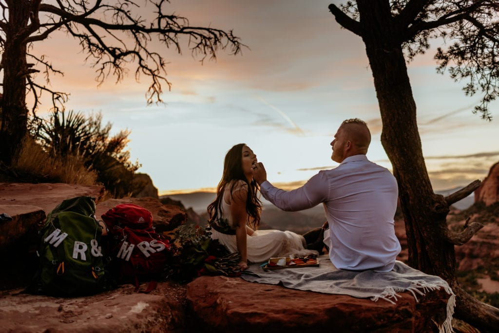 Groom feeding bride picnic