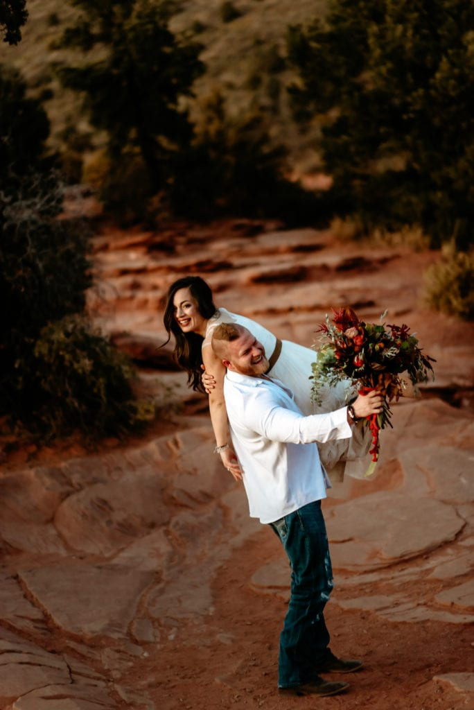 groom carrying bride over his shoulder laughing