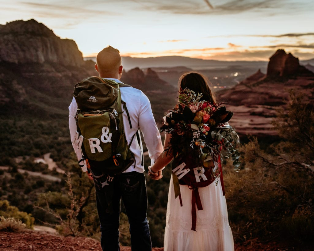 Elopement couple holding hands with their backpacks overlooking Sedona