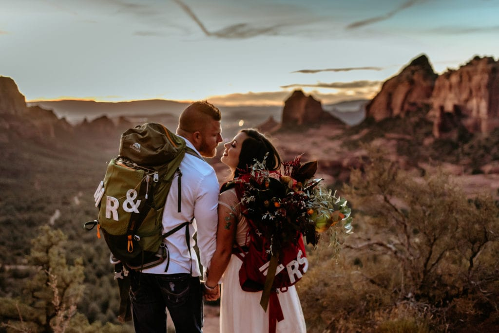 Couple in backpacks kiss during Sedona Sunset