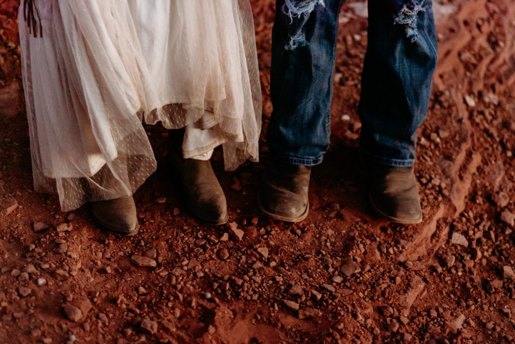 Cowboy boots and red rock dust Ombre on wedding dress during Merry Go Round Rock wedding