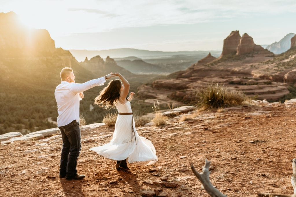 Couple dancing on Merry Go Round Rock ledge overlooking Sedona, Arizona on their elopement day