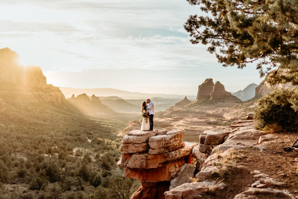 Couple embracing on Merry Go Round Rock overlook during their Sedona, Arizona elopement