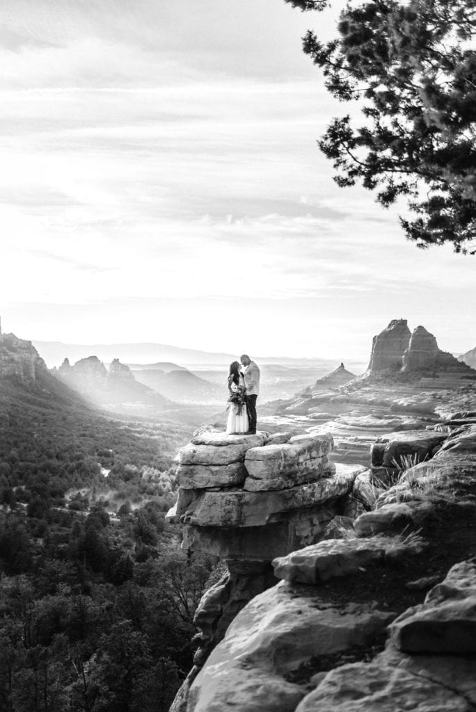 Dramatic black and white image of couple embracing at Carousel Rock in Sedona