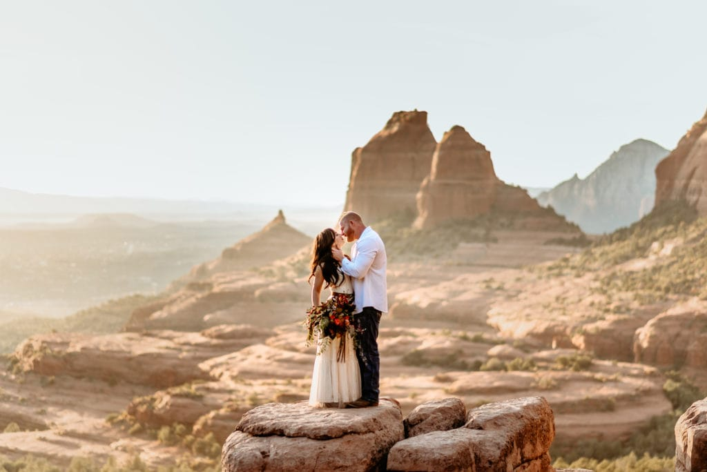 Groom gazing at his wife overlooking Sedona on a red rock ledge