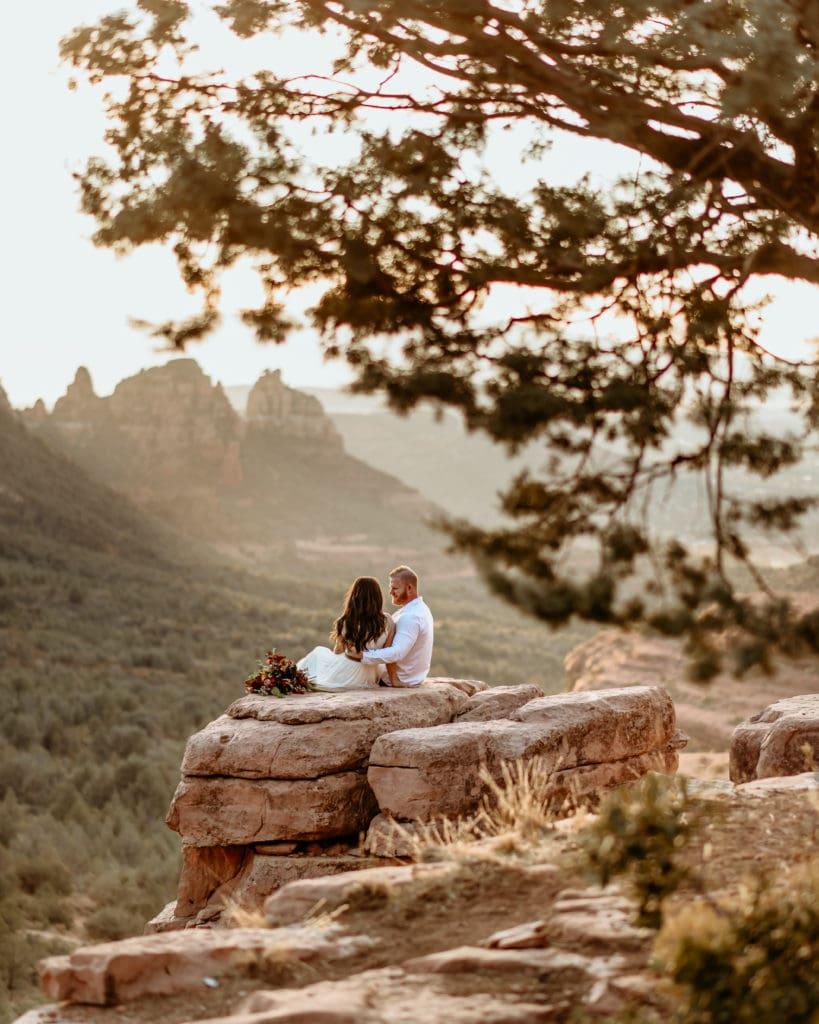 Wedding couple watching the sun set behind the mountains in Sedona, Arizona