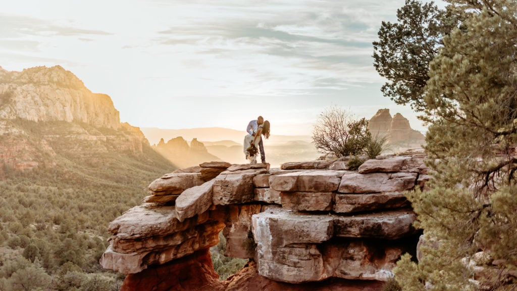 Groom dips bride into a kiss at Carousel Rock in Sedona