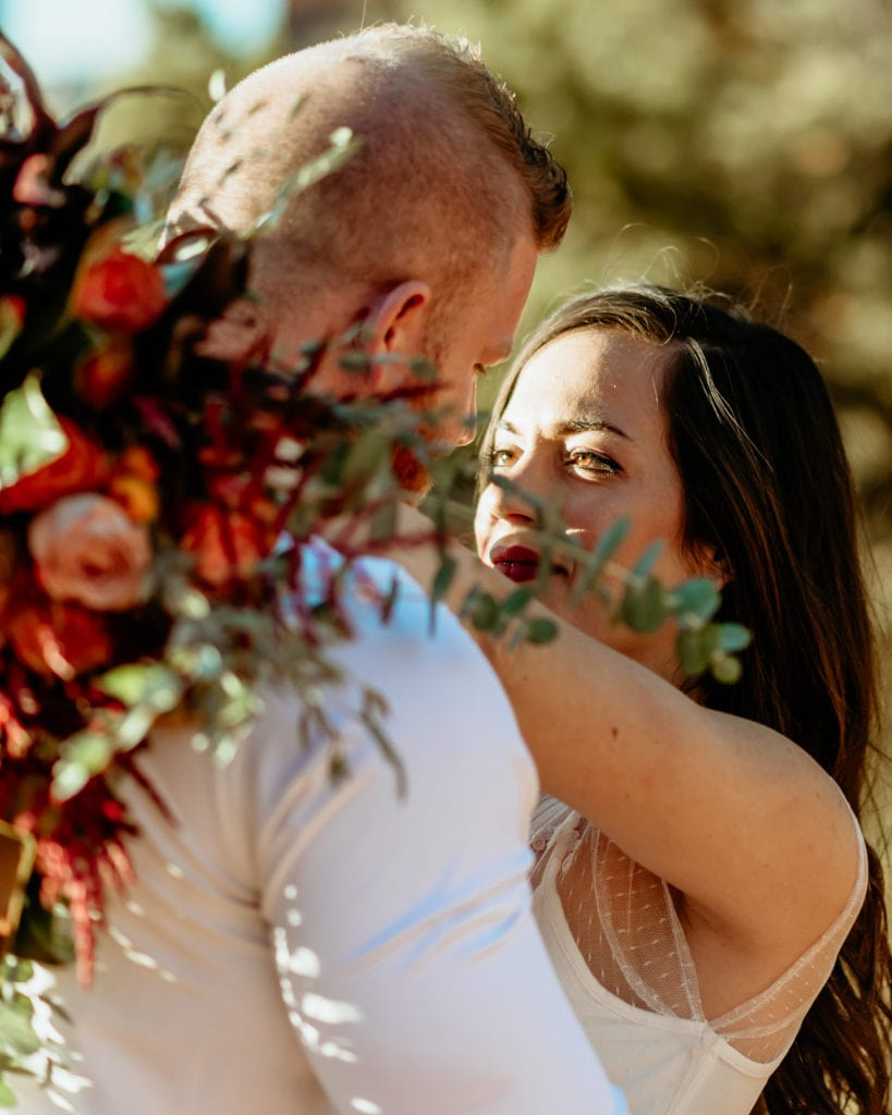 Bride gazing in to grooms eyes with a giant fall colored wildflower bouquet