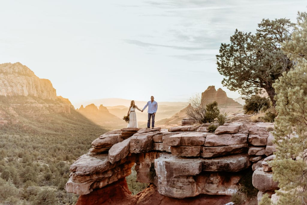 Elopement couple standing on Merry Go Round Rock as the sunset lights up the sky behind them