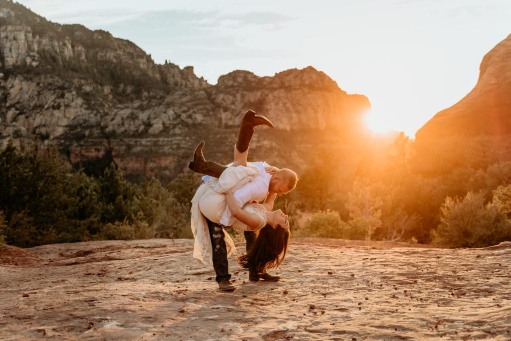 Groom dips bride as they dance on a large red rock