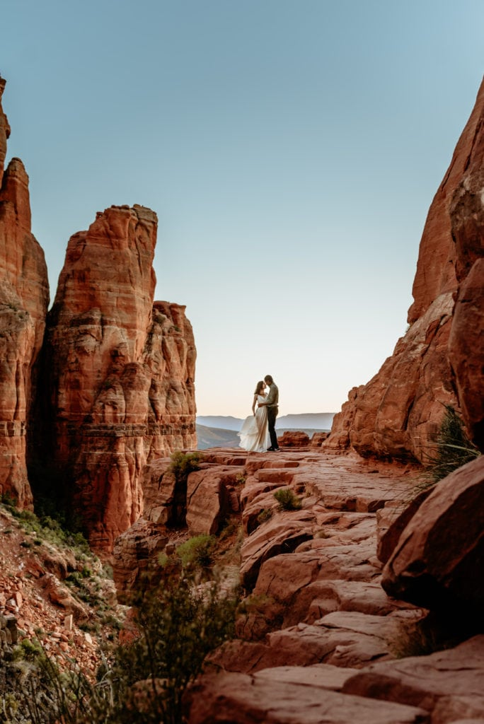 Couple embrace at the edge of the Cathedral Rock summit