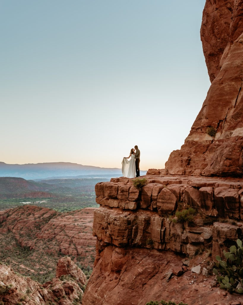 Romantic embrace on the ledge overlooking Sedona at the top of Cathedral Rock