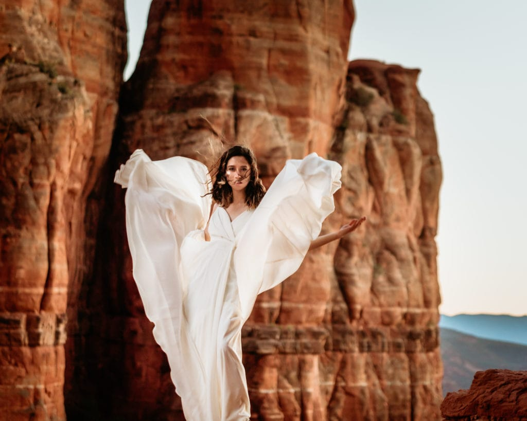 Red rock angel bridals as the wind flies through the flowing dress during sunset in Sedona