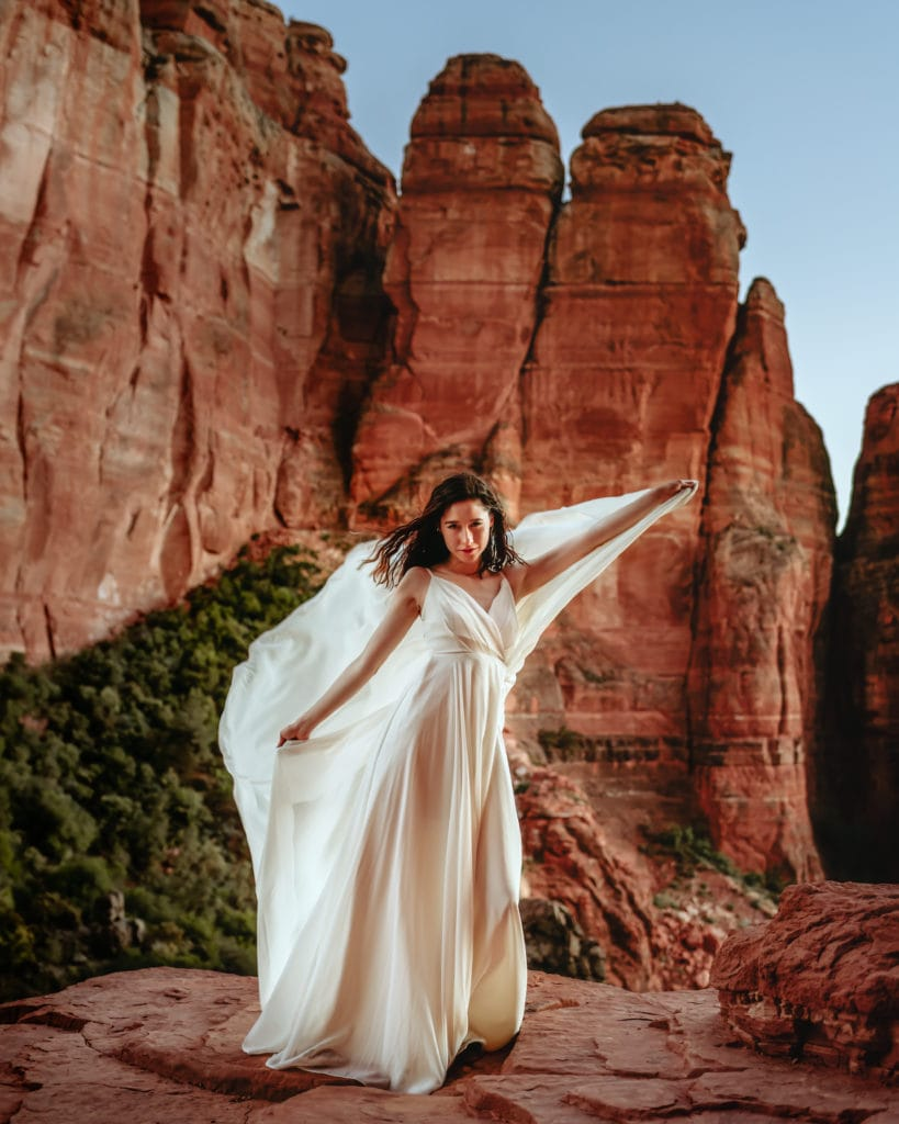 Bride holding flowing wedding dress as a cape on her Cathedral Rock elopement in Sedona, AZ