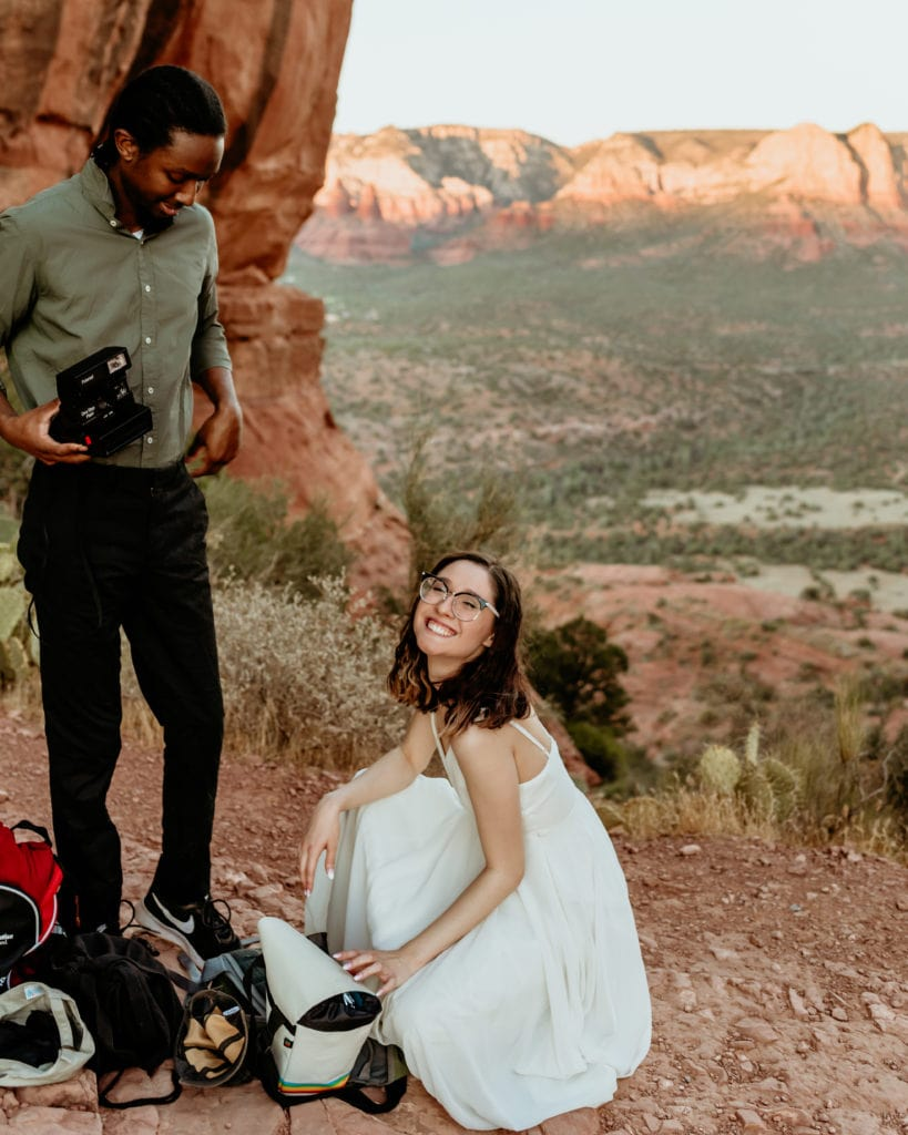 Couple smiling with excitement while getting dressed in their elopement clothing at the top of Cathedral Rock
