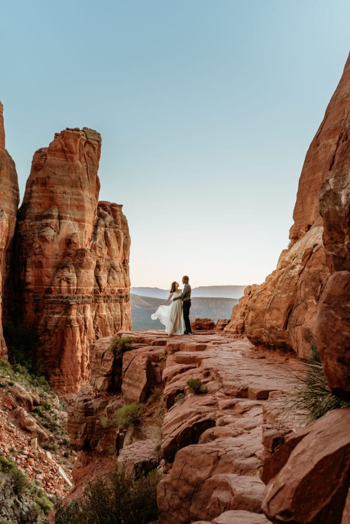 Sunset glow and blue skies enveloping elopement couple at the peak of Cathedral Rock in Sedona