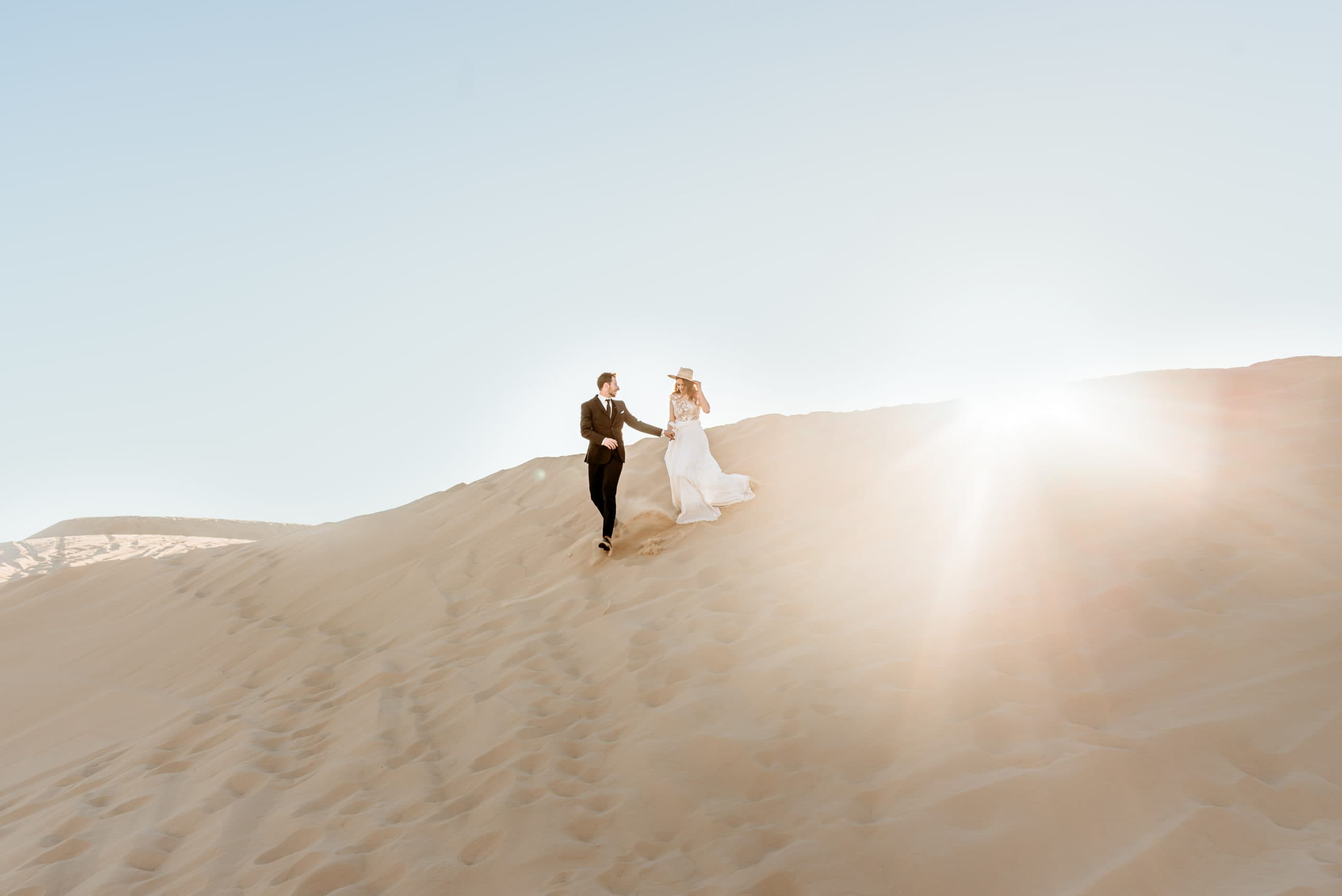 wedding couple holding hands running down a sand dune