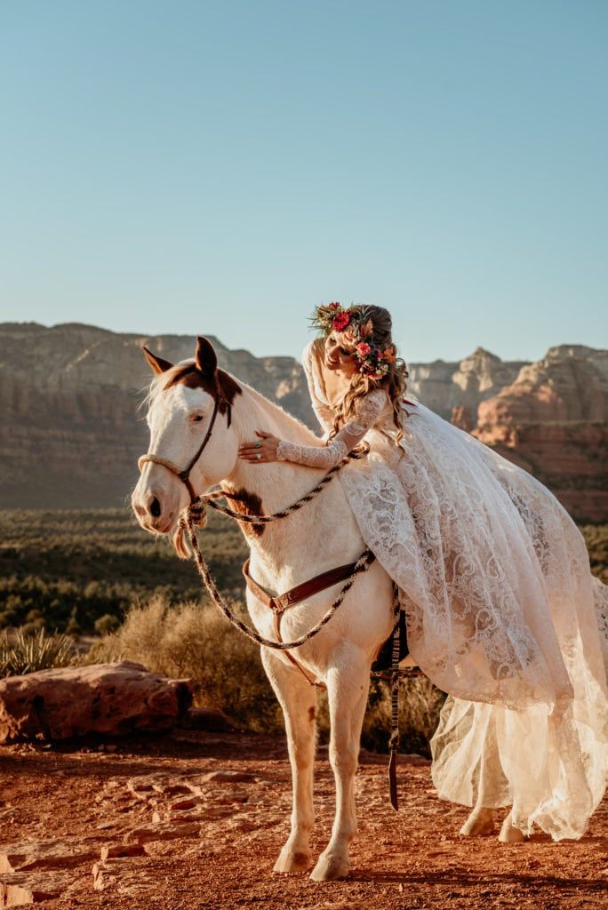 Bride in a long lace dress and floral crown on a horse overlooking Sedona's red rocks