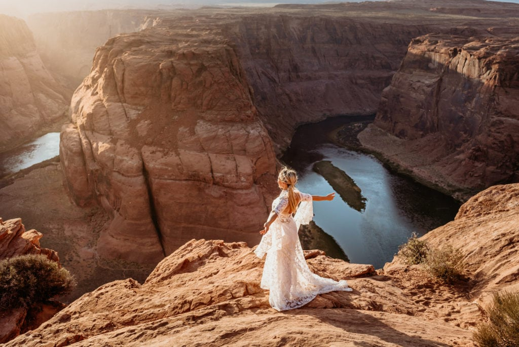 Bride standing arms outstretched as the wind blows and sun shines against her face at the edge of Horseshoe Bend in Page, Arizona