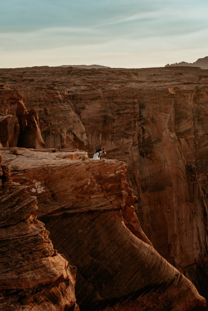 Groom dipping bride into a deep kiss overlooking a giant canyon in Page, Arizona