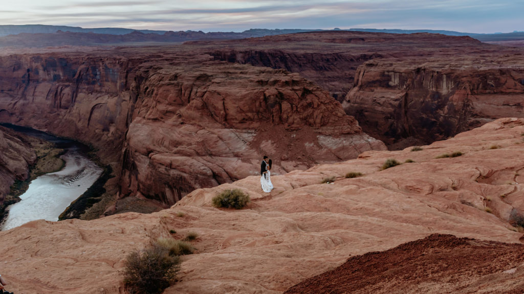 Wide view of couple looking down on the Colorado River