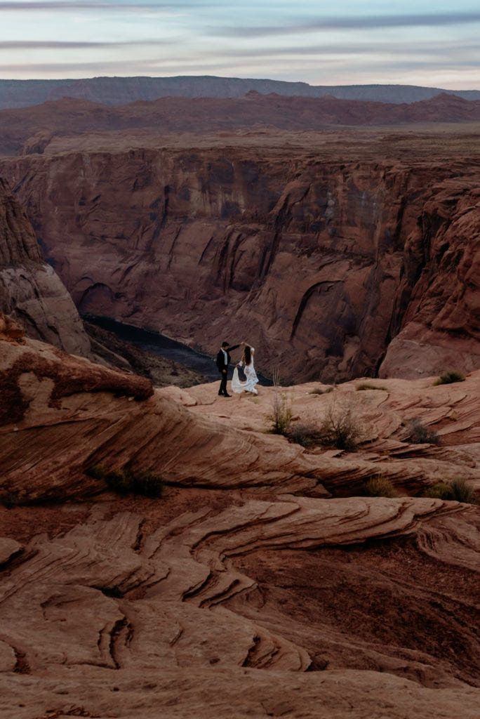 Elopement couple dancing at the edge of Horseshoe Bend