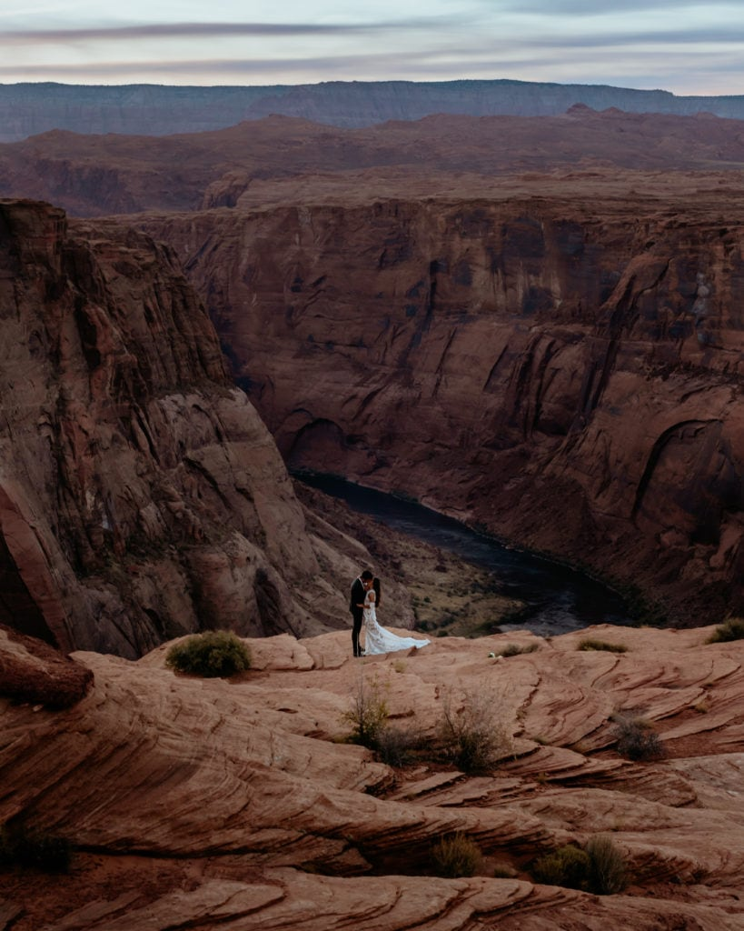 Looking down on the Colorado River and couple on the ledge in Page, Arizona