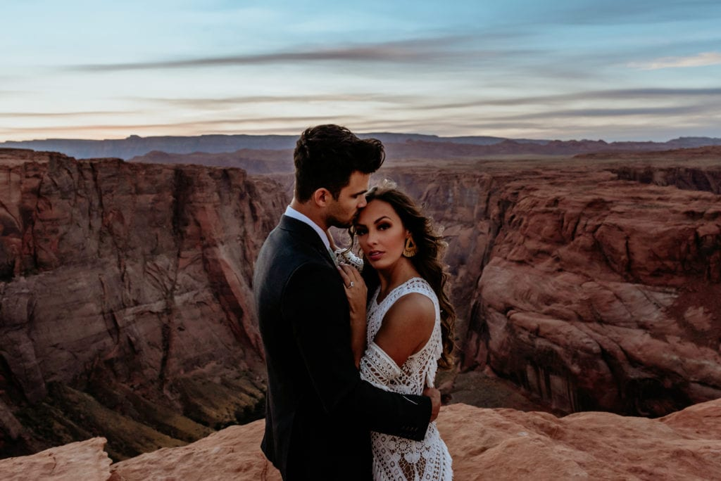 Elopement couple embrace in front of Horseshoe Bend canyon