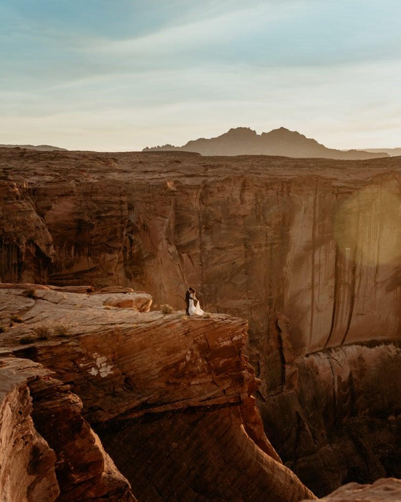 Couple embrace on a far ledge of Horseshoe Bend in Arizona