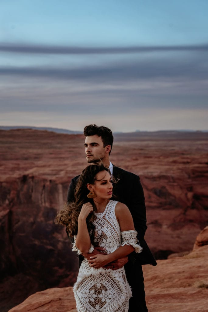 Wind sweeps bride's hair as she and groom look into the distance during Page sunset elopement