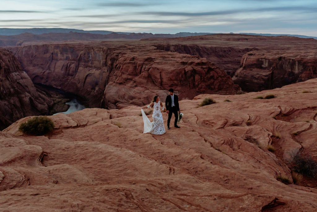 Elopement couple walk hand in hand up the sandstone at Horseshoe Bend