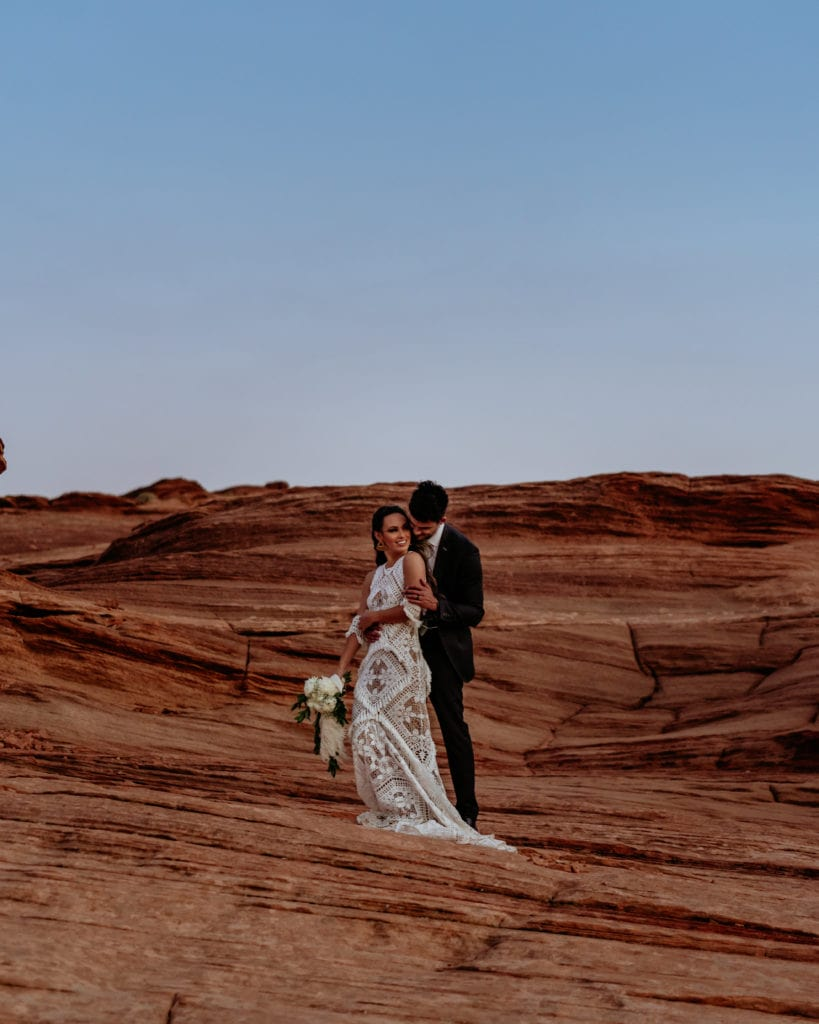 Bride and groom looking off into the sunset from sandstone ledge