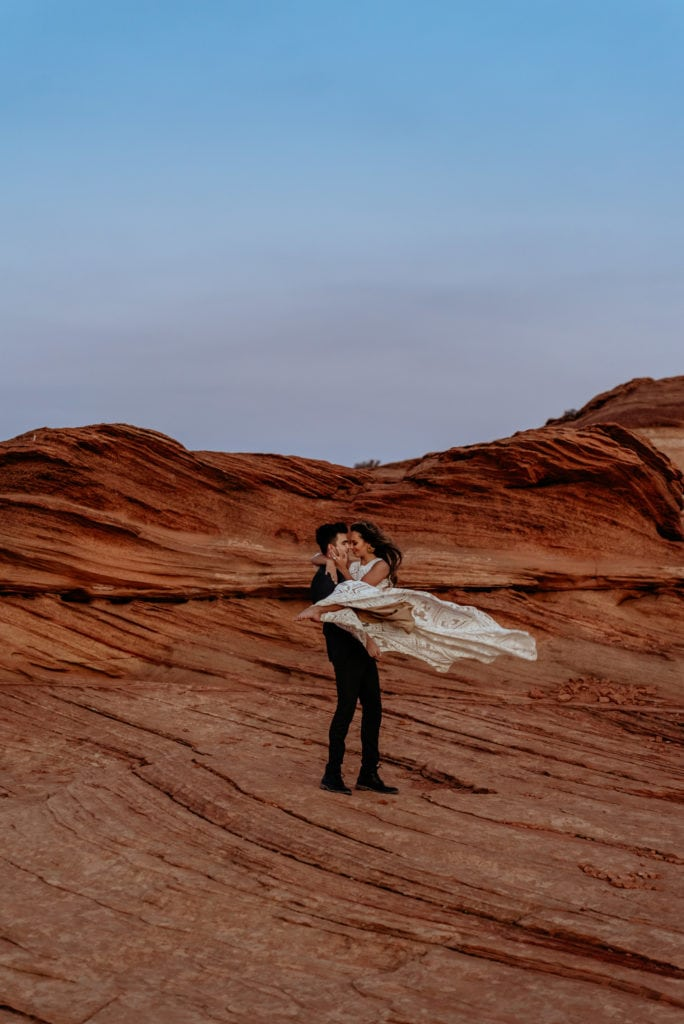 Groom swinging bride through the air as her Rue De Seine Lace Boho wedding dress flies behind her