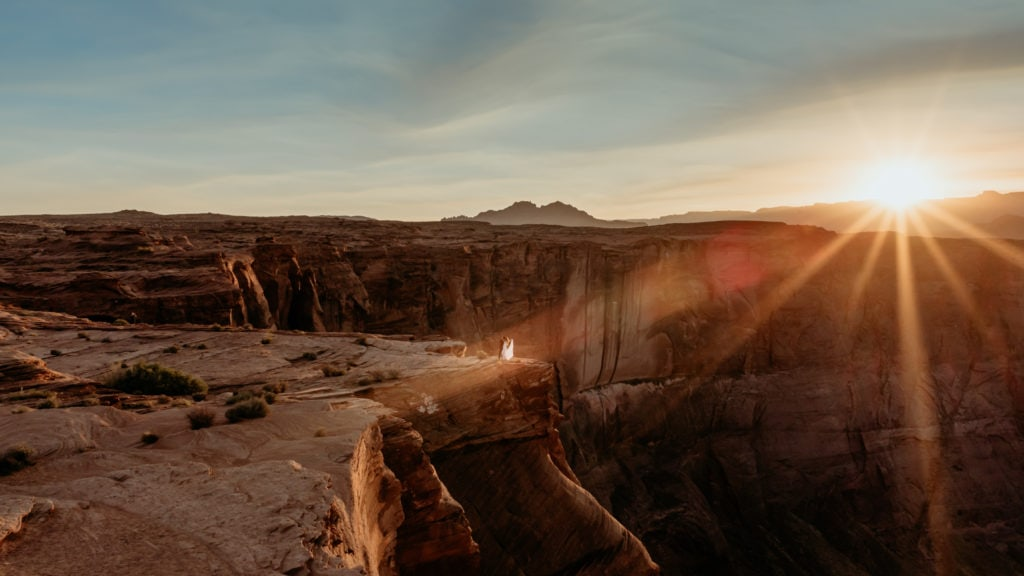 Bride and groom dance at the edge of a deep sandstone ledge at Horseshoe Bend