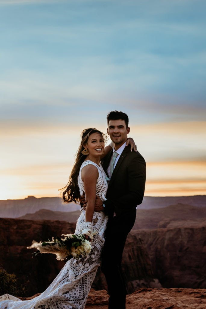 Bride and groom smile at sunset