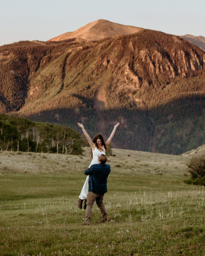 Groom spinning his bride as they run and play during their Colorado elopement