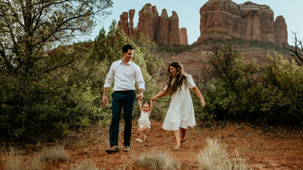 Couple walks and swings their little girl with Cathedral Rock in the background