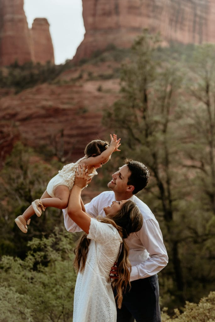 Mom and Dad hold their little girl up in the air at the base of Cathedral Rock in Sedona