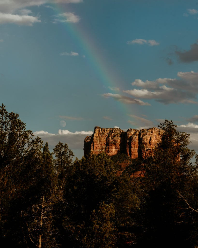 Rainbow overlooking the moon rising during a hiking elopement in Sedona Arizona