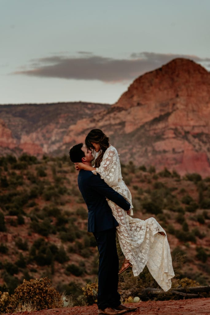 Husband lifts his wife in her long lace dress surrounded by Sedona red rocks at sunset