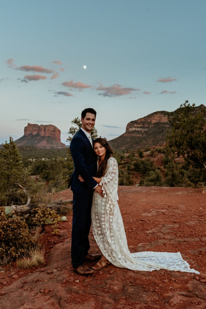 Husband and wife embrace as the moon rises over Capitol Butte in the distance