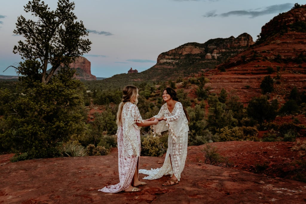 Bride and maid of honor dance and laugh at Sedona ceremony