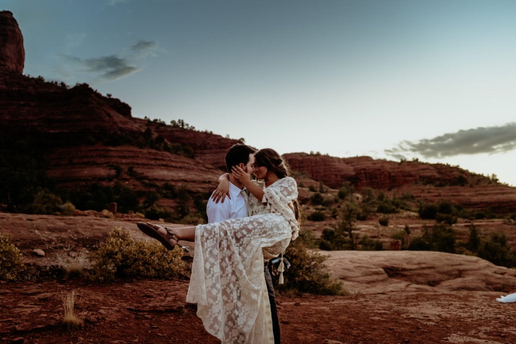 Husband holds and spins wife as the very last of the sunlight dips behind the red rocks of Cathedral Rock
