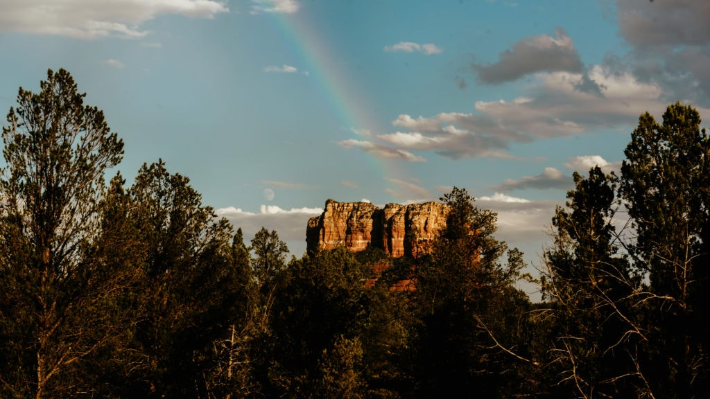 Rainbow perfectly placed after a brief rain over Capitol Butte Rock with moon rising in the distance