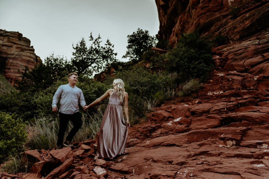 Couple walking hand in hand through red rock canyon