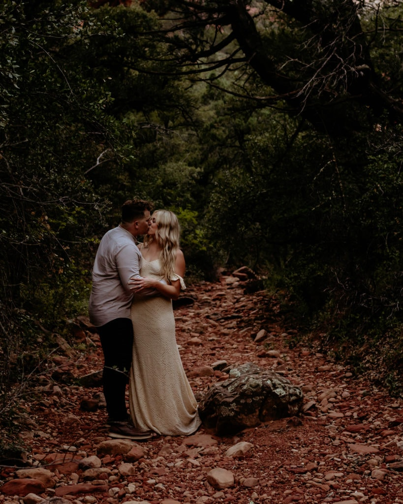 Elopement couple embrace in a secluded Sedona wash surrounded by green trees and red rocks